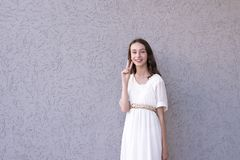 Lady in pretty dress showing peace sign. Smiling beautiful model showing peace sign. Well-dressed happy girl. Attractive young woman with wavy luxury hairstyle stock photo