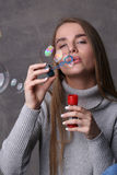 Lady in pullover blowing bubbles. Close up. Gray background Royalty Free Stock Photo