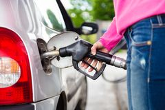 Lady pumping gasoline fuel in car at gas station. Closeup of woman pumping gasoline fuel in car at gas station. Petrol or gasoline being pumped into a motor stock image