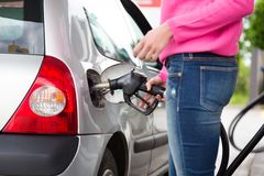 Lady pumping gasoline fuel in car at gas station. Royalty Free Stock Photos