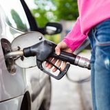 Lady pumping gasoline fuel in car at gas station. Stock Image
