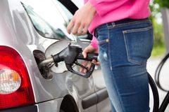 Lady pumping gasoline fuel in car at gas station. Stock Photography