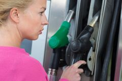 Lady pumping gasoline fuel in car at gas station. Royalty Free Stock Photo