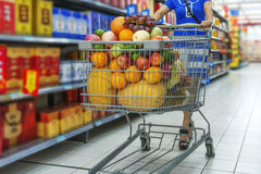 A lady pushing a shopping cart in the mall shopping Stock Images