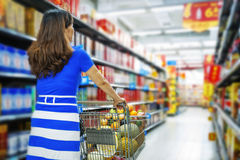 A lady pushing a shopping cart in the mall shopping Stock Photos
