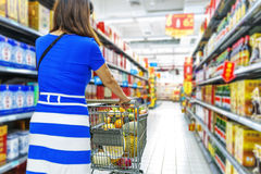 A lady pushing a shopping cart in the mall shopping Royalty Free Stock Photography