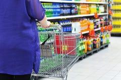 Lady pushing a shopping cart Royalty Free Stock Images