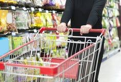 Lady pushing a shopping cart Royalty Free Stock Photos