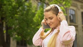 Lady putting on headphones and listening to music on mobile, new app downloading. Stock footage stock video