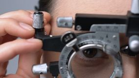 Lady putting on ophthalmic testing device for eye examination and lens selection stock video footage