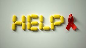 Lady putting red ribbon near help word made of pills on table, AIDS awareness. Stock photo stock images