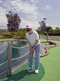 Lady Putting From The Rough. This miniature golf course even has some rough areas to putt from Stock Image