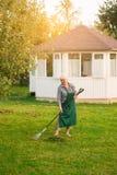 Lady with rake in garden. Royalty Free Stock Photos