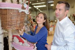 Lady reaching for wicker basket in shop. Wicker royalty free stock photos