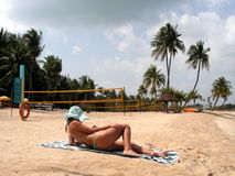 Lady reading on beach. Resort living with sun tanning. Relaxation at its best. Reading in the sun. Volleyball nets next to her Stock Photos