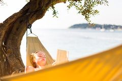 Lady reading book in hammock. Royalty Free Stock Images