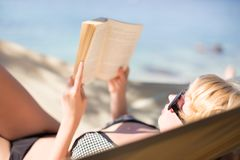 Lady reading a book in a hammock. Stock Image