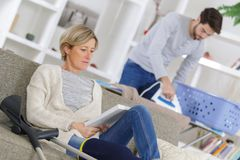 Lady reading book while home help assistant ironing. Lady reading a book while home help assistant is ironing Stock Photography