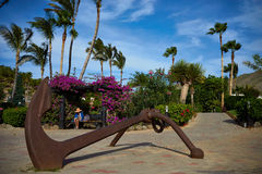 Lady reading book in peace in great atmosphere with bougainvillea and palm trees with big anchor in foreground. Lady reading book in sunshine on bench with stock image