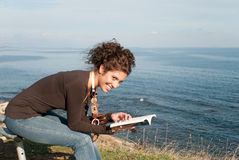 Lady reading a book at the seaside Stock Photo