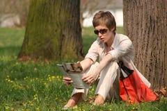 Lady is reading magazine. Lady sitting at the tree is reading magazine Stock Image