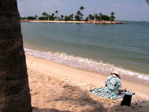 Lady reading on seashore. Resort living with sun tanning. Relaxation at its best. Reading in the sun Royalty Free Stock Photos