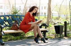Lady reads on bench in park Royalty Free Stock Images