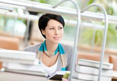 Lady reads sitting at the desk Stock Photography