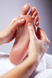 Lady Receiving Foot Massage. Female foot being massaged on a white towel Stock Image