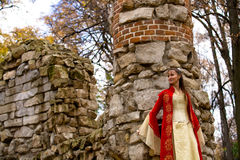 Lady in red. Lady in medieval red dress standing near old wall stock images