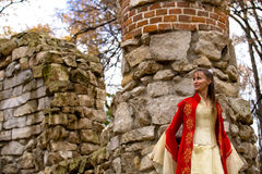 Lady in red. Lady in medieval red dress standing near old wall royalty free stock images