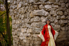 Lady in red. Lady in medieval red dress standing near old wall stock photos