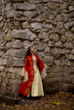 Lady in red. Lady in medieval red dress standing near old wall stock image
