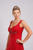 Lady in red. Adult attractive woman in a red evening gown with a neckline and bare shoulders Stock Image