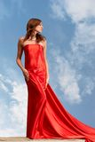 Lady in red. Photo of graceful female folded in bright red silk shawl with cloudy sky at background Stock Images