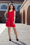 Lady in red. Handsome girl dressed in red short skirt standing outside in urban landscape in a sunny day Stock Photography
