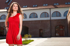 Lady in red. Handsome girl dressed in red short skirt standing outside in urban landscape in a sunny day Royalty Free Stock Photography