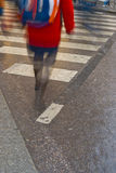 Lady in red. A lady in red walking on a wet Zebra crossing Stock Photos