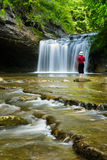 Lady in Red. Barefoot woman standing on a stone at on of the beautiful Cascades du Herisson in France Stock Photos