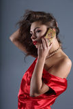 Lady in red. Beautiful girl in a red silk dress talking on mobile phone stock photo