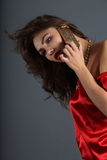 Lady in red. Beautiful girl in a red silk dress talking on mobile phone royalty free stock photo