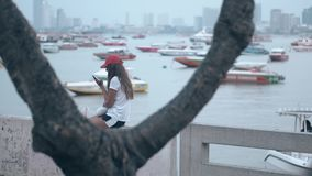 Lady in red cap reads sms in phone sitting against sea bay. Lady in red cap white t-shirt reads sms in phone sitting on parapet against sea bay with boats view stock footage
