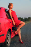 Lady in red and car. The red-haired beauty in a red evening dress near the red car on a decline Royalty Free Stock Image