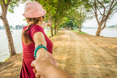 Lady in red cloth pointing her finger and leads her lover by the hand on the paved road Royalty Free Stock Photos