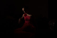 Lady in red in a dark room Stock Photo