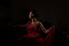 Lady in red in a dark room Stock Photography