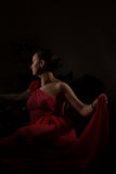 Lady in red in a dark room Royalty Free Stock Photography