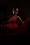Lady in red in a dark room Stock Image