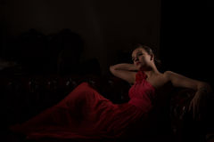 Lady in red in a dark room Royalty Free Stock Photos