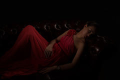 Lady in red in a dark room Royalty Free Stock Photo